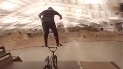 Here's A Guy Riding His BMX By Standing On The Handlebars While Going Round A Skate Park