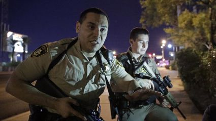 Police officers advise people to take cover near the scene of the shooting near the Mandalay Bay resort on the Las Vegas Strip today. Photo / AP / NZ Herald